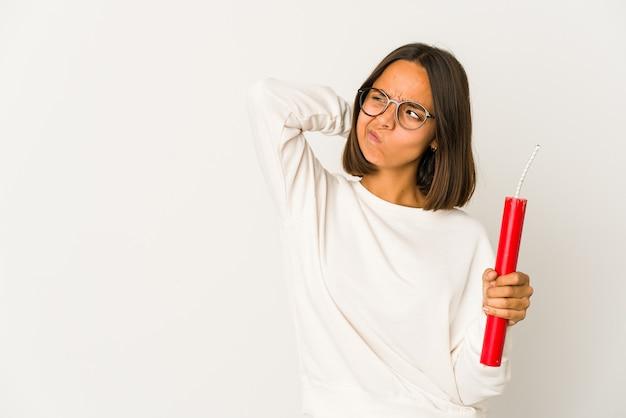 Mulher jovem de raça mista hispânica segurando uma dinamite tocando a parte de trás da cabeça, pensando e fazendo uma escolha.