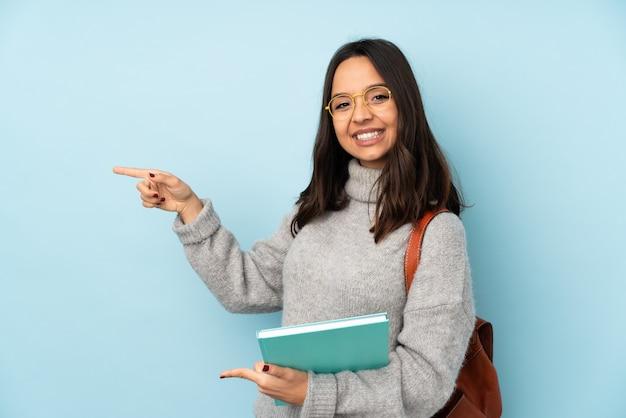 Mulher jovem de raça mista, indo para a escola isolada na parede azul, apontando o dedo para o lado e apresentando um produto