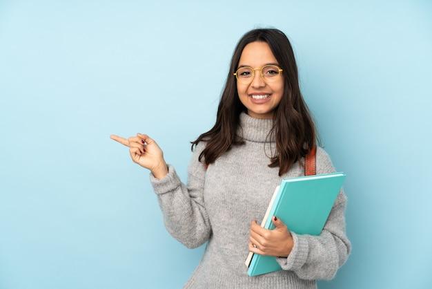 Mulher jovem de raça mista, indo para a escola na parede azul, apontando o dedo para o lado