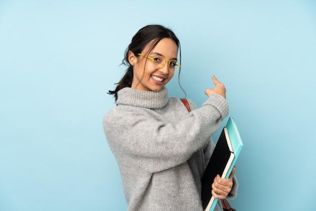 Mulher jovem de raça mista, indo para a escola na parede azul, apontando para trás