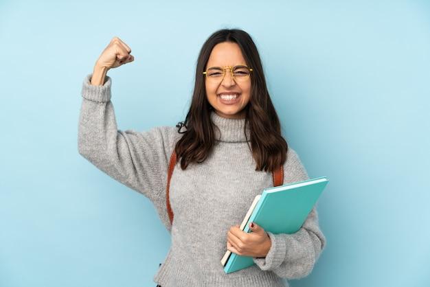 Mulher jovem de raça mista, indo para a escola na parede azul, fazendo um gesto forte