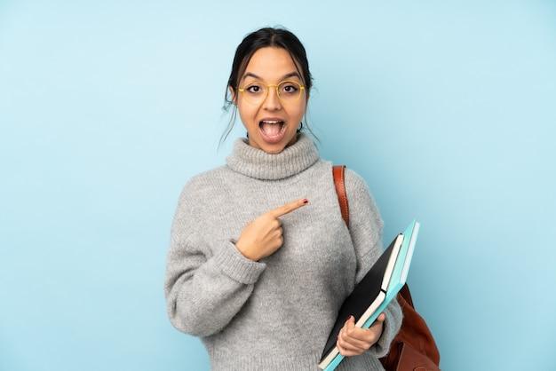 Mulher jovem de raça mista, indo para a escola no lado azul surpreso e apontando