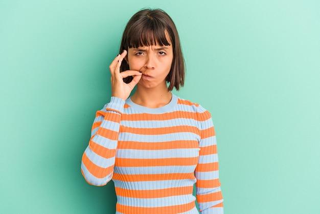 Mulher jovem de raça mista isolada em azul com os dedos nos lábios, mantendo um segredo.
