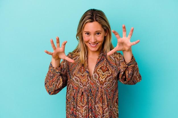 Mulher jovem de raça mista isolada em azul mostrando garras imitando um gato, gesto agressivo.