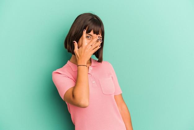 Mulher jovem de raça mista isolada em azul pisca para a câmera por entre os dedos, rosto cobrindo vergonha.