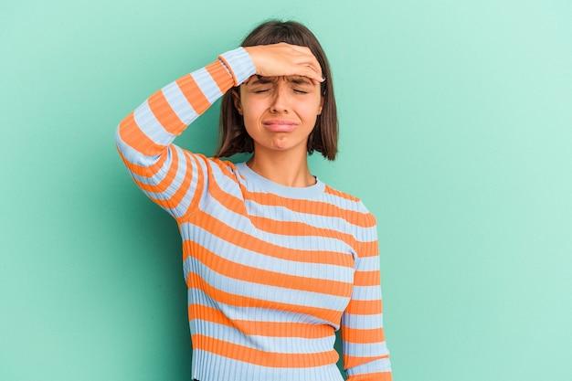Mulher jovem de raça mista isolada em azul tocando templos e tendo dor de cabeça.