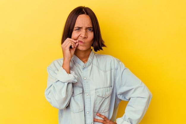 Mulher jovem de raça mista isolada em fundo amarelo com os dedos nos lábios, mantendo um segredo.