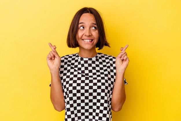 Mulher jovem de raça mista isolada em fundo amarelo cruzando os dedos para ter sorte