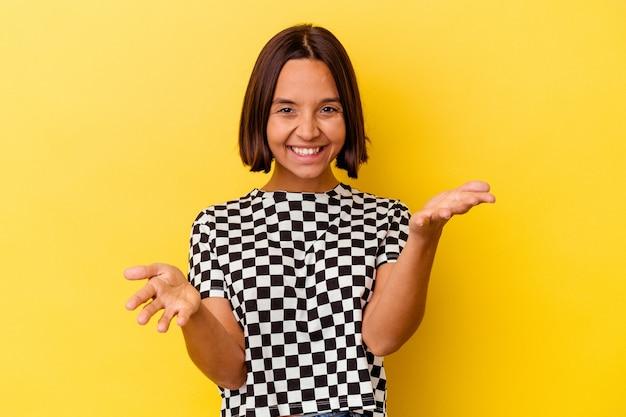Mulher jovem de raça mista isolada em fundo amarelo se sente confiante em dar um abraço para a câmera.