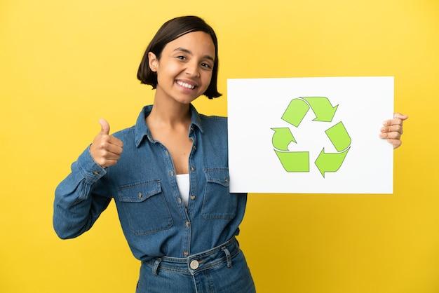 Mulher jovem de raça mista isolada em fundo amarelo segurando um cartaz com o ícone de reciclagem com o polegar para cima