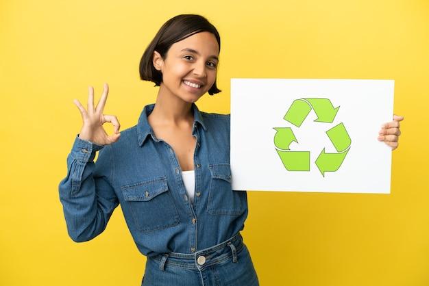Mulher jovem de raça mista isolada em fundo amarelo segurando um cartaz com o ícone de reciclagem e comemorando uma vitória
