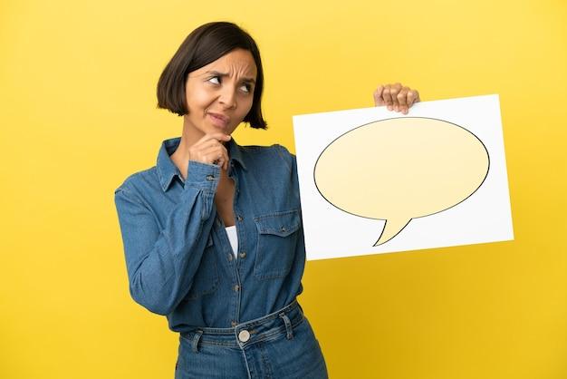 Mulher jovem de raça mista isolada em fundo amarelo segurando um cartaz com o ícone de um balão de fala e pensando