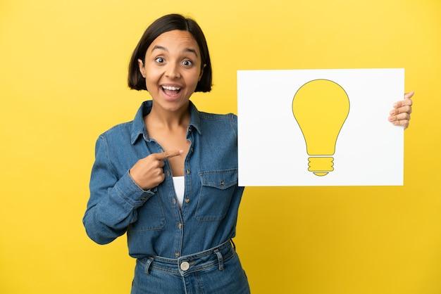 Mulher jovem de raça mista isolada em fundo amarelo segurando um cartaz com o ícone de uma lâmpada e apontando-o
