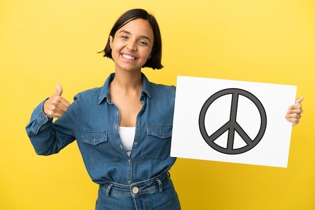 Mulher jovem de raça mista isolada em fundo amarelo segurando um cartaz com o símbolo da paz com o polegar para cima