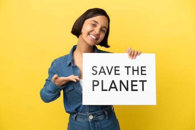Mulher jovem de raça mista isolada em fundo amarelo segurando um cartaz com o texto salve o planeta e apontando-o