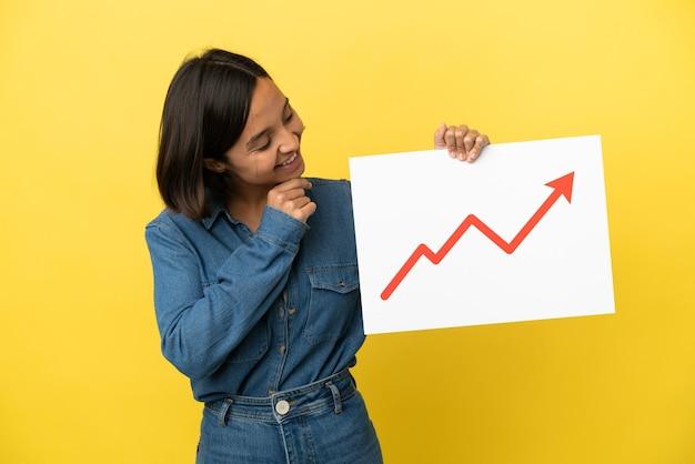 Mulher jovem de raça mista isolada em fundo amarelo segurando uma placa com um símbolo de seta de estatísticas crescentes e pensando