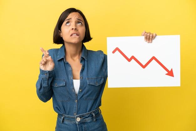 Mulher jovem de raça mista isolada em fundo amarelo segurando uma placa com um símbolo de seta de estatísticas decrescente cruzando os dedos