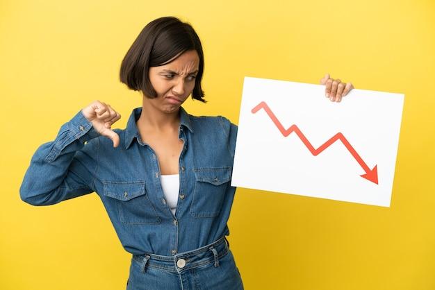 Mulher jovem de raça mista isolada em fundo amarelo segurando uma placa com um símbolo de seta de estatísticas decrescentes e fazendo um sinal ruim