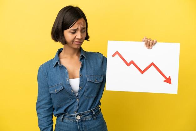Mulher jovem de raça mista isolada em fundo amarelo segurando uma placa com um símbolo de seta decrescente de estatísticas com uma expressão triste