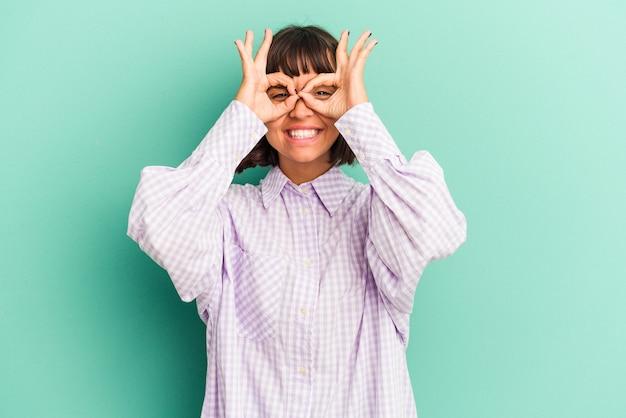 Mulher jovem de raça mista isolada em fundo azul, apontando com o dedo para você como se fosse um convite para se aproximar.