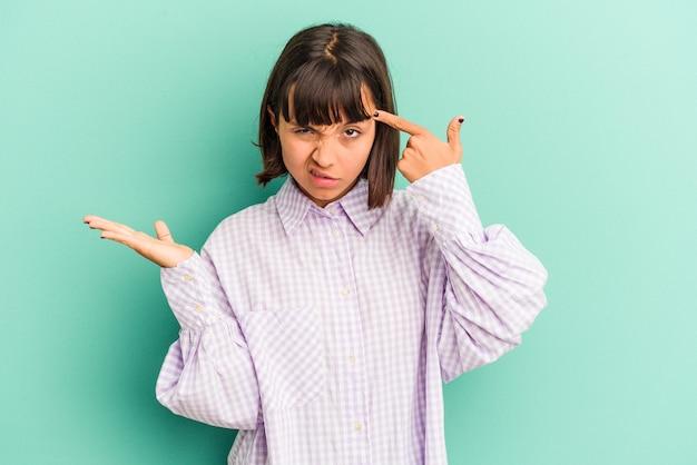 Mulher jovem de raça mista isolada em fundo azul cruzando os dedos para ter sorte