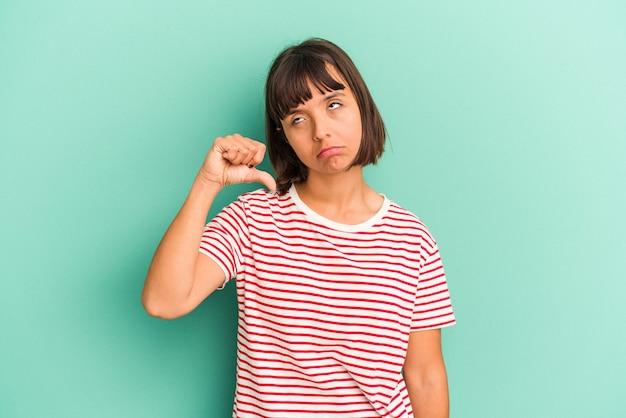 Mulher jovem de raça mista isolada em fundo azul, dizendo uma fofoca, apontando para o lado relatando algo.