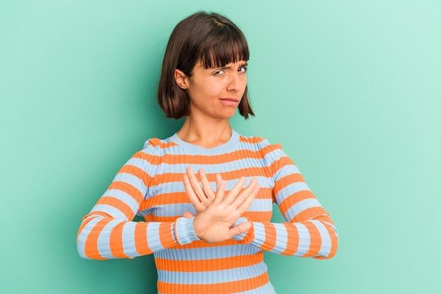Mulher jovem de raça mista isolada em fundo azul faz escala com os braços, sente-se feliz e confiante.