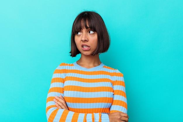 Mulher jovem de raça mista isolada em fundo azul infeliz olhando na câmera com expressão sarcástica.