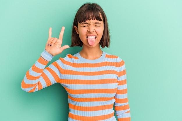 Mulher jovem de raça mista isolada em fundo azul mostrando os polegares para cima e para baixo, difícil escolher o conceito