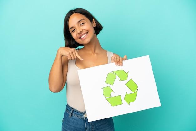 Mulher jovem de raça mista isolada em fundo azul segurando um cartaz com o ícone de reciclagem e apontando-o