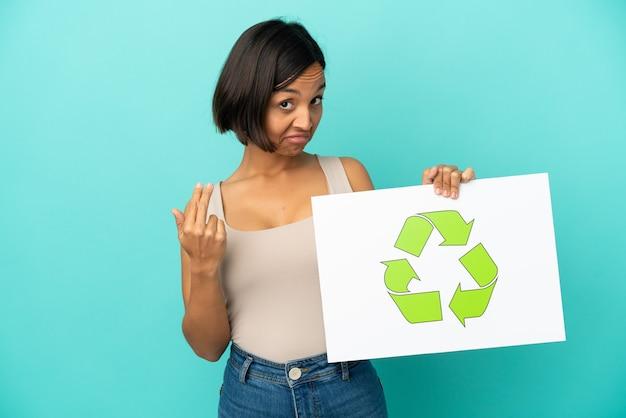 Mulher jovem de raça mista isolada em fundo azul segurando um cartaz com o ícone de reciclagem e fazendo gesto de vinda