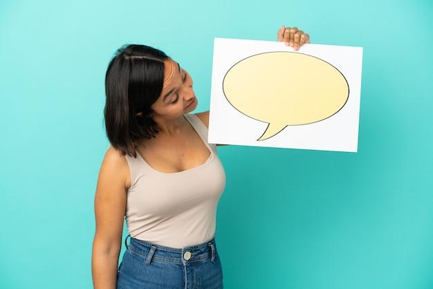 Mulher jovem de raça mista isolada em fundo azul segurando um cartaz com o ícone de um balão de fala