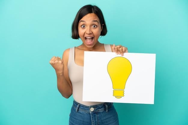 Mulher jovem de raça mista isolada em fundo azul segurando um cartaz com o ícone de uma lâmpada e comemorando uma vitória