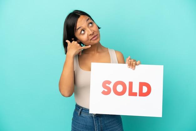 Mulher jovem de raça mista isolada em fundo azul segurando um cartaz com o texto vendido e fazendo gesto de vinda