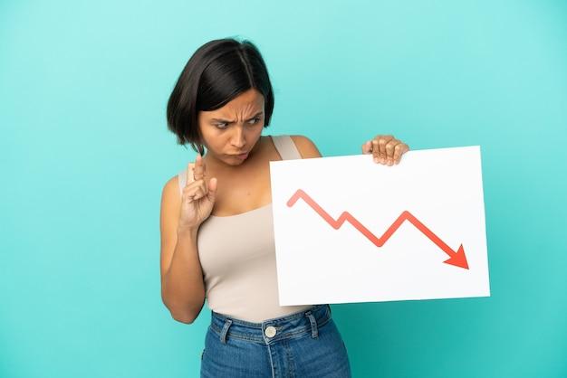 Mulher jovem de raça mista isolada em fundo azul segurando uma placa com um símbolo de seta de estatísticas decrescente cruzando os dedos