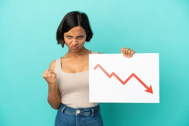 Mulher jovem de raça mista isolada em fundo azul segurando uma placa com um símbolo de seta de estatísticas decrescentes e com raiva