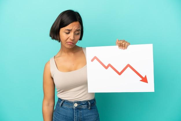 Mulher jovem de raça mista isolada em fundo azul segurando uma placa com um símbolo de seta decrescente de estatísticas com expressão triste
