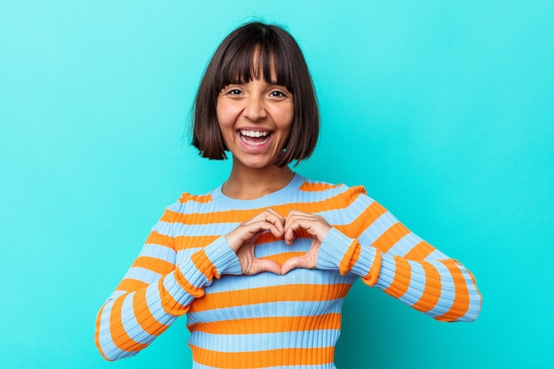 Mulher jovem de raça mista isolada em fundo azul, sorrindo e mostrando uma forma de coração com as mãos.
