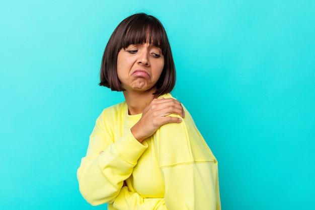 Mulher jovem de raça mista isolada em fundo azul, tendo uma dor no ombro.