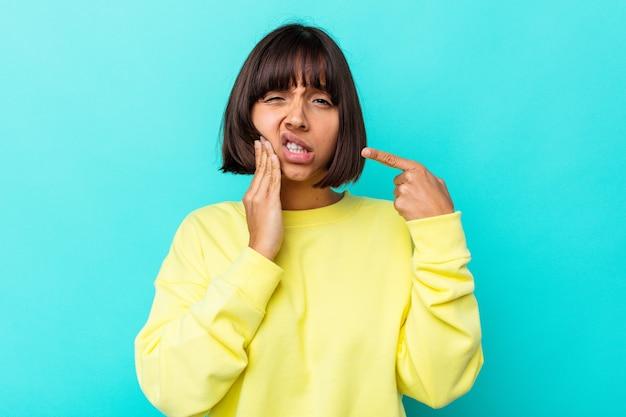 Mulher jovem de raça mista isolada em fundo azul, tendo uma forte dor nos dentes, dor molar.