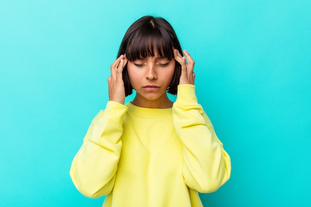 Mulher jovem de raça mista isolada em fundo azul, tocando as têmporas e tendo dor de cabeça.