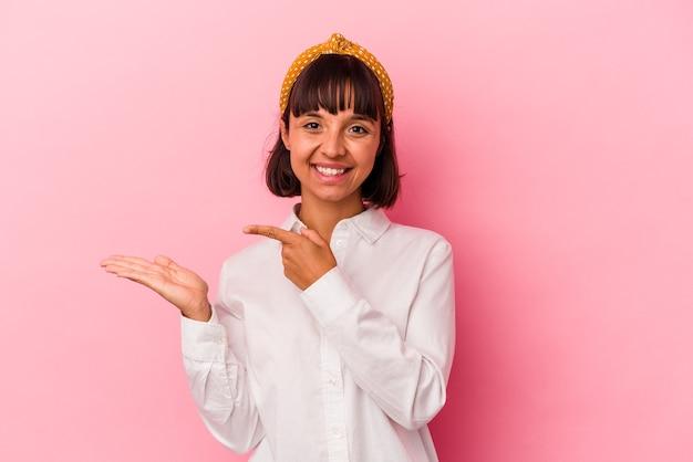 Mulher jovem de raça mista isolada em fundo rosa animado segurando um espaço de cópia na palma da mão.