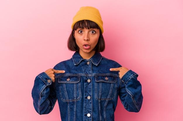 Mulher jovem de raça mista isolada em fundo rosa aponta para baixo com os dedos, sentimento positivo.
