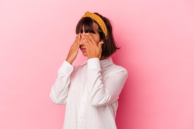 Mulher jovem de raça mista isolada em fundo rosa com medo de cobrir os olhos com as mãos.