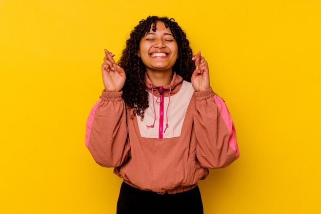 Mulher jovem de raça mista isolada em fundo rosa cruzando os dedos para ter sorte