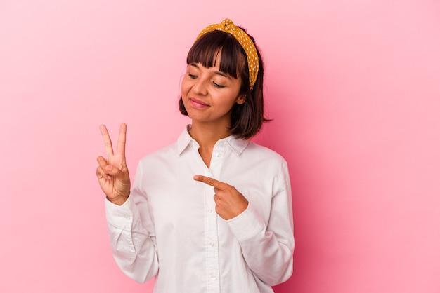 Mulher jovem de raça mista isolada em fundo rosa, fazendo um juramento, colocando a mão no peito.