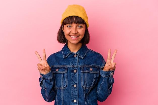 Mulher jovem de raça mista isolada em fundo rosa, mostrando sinal de vitória e sorrindo amplamente.