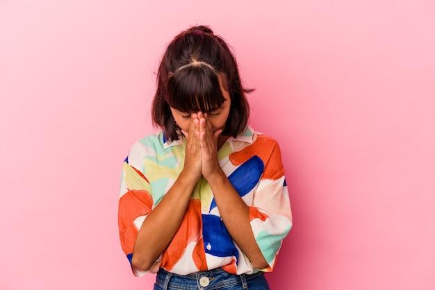 Mulher jovem de raça mista isolada em fundo rosa orando, mostrando devoção, pessoa religiosa em busca de inspiração divina.