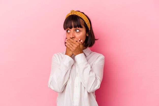 Mulher jovem de raça mista isolada em fundo rosa pensativo olhando para um espaço de cópia cobrindo a boca com a mão.
