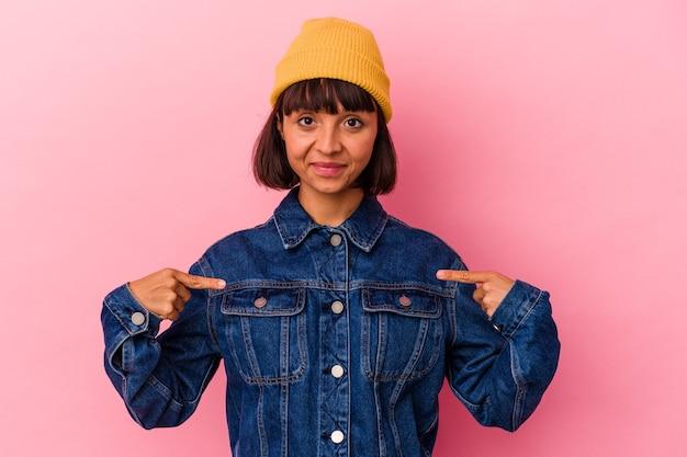 Mulher jovem de raça mista isolada em fundo rosa pessoa apontando com a mão para um espaço de cópia de camisa, orgulhosa e confiante